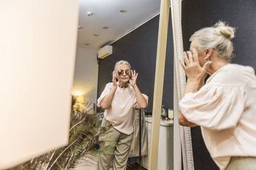 Senior woman trying on sunglasses in a boutique - VGF00029