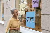Senior woman looking in shop window of a boutique - VGF00038