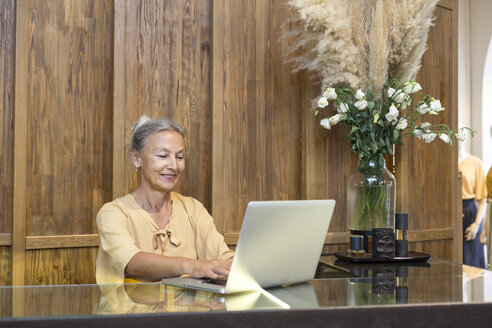 Smiling senior woman using laptop at reception desk - VGF00041