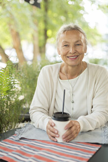 Portrait of smiling senior woman at an outdoor cafe - VGF00044