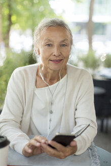 Portrait of senior woman at an outdoor cafe with cell phone and earphones - VGF00053