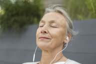 Portrait of senior woman with closed eyes wearing earphones outdoors - VGF00059