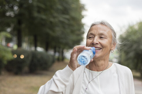 Happy senior woman outdoors drinking water from bottle - VGF00065
