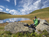 Italy, Lombardy, hiker sitting at lake and eating an apple - LAF02101