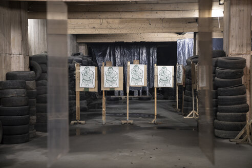 Boards with male likeness as targets in an indoor shooting range - KKAF02577