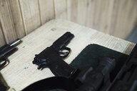 Pistol on table in an indoor shooting range - KKAF02580