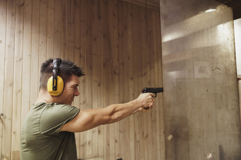 Man aiming with a pistol in an indoor shooting range - KKAF02583