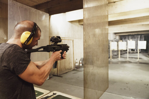 Man aiming with a rifle in an indoor shooting range - KKAF02586