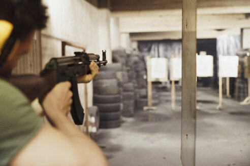 Man aiming with a rifle in an indoor shooting range - KKAF02589