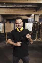 Portrait of man holding a rifle in an indoor shooting range - KKAF02592