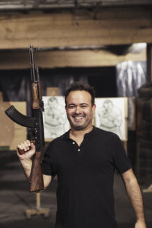 Portrait of smiling man holding a rifle in an indoor shooting range - KKAF02595