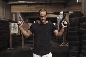 Portrait of man posing with two guns in an indoor shooting range - KKAF02598