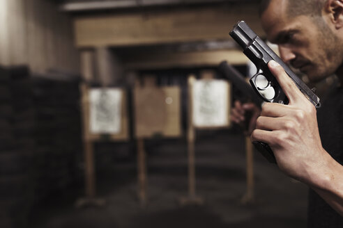 Close-up of man posing with two guns in an indoor shooting range - KKAF02601