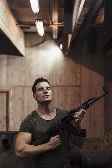 Portrait of man holding a rifle in an indoor shooting range - KKAF02604