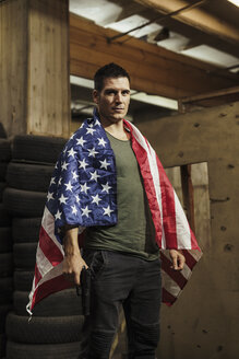 Portrait of man wearing American flag holding a gun - KKAF02610