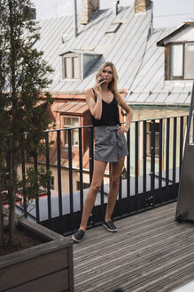 Serious blond woman on the phone standing on roof terrace - KKAF02619