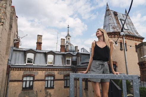 Young woman standing on balcony enjoying fresh air - KKAF02628