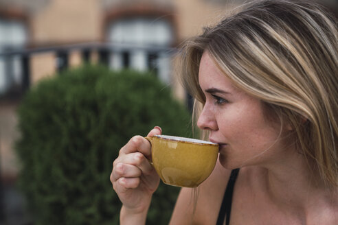 Young woman drinking cup of coffee - KKAF02631