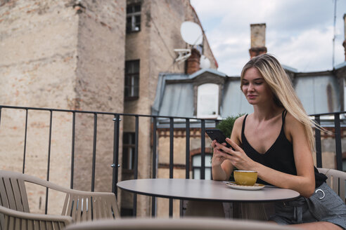 Smiling blond woman sitting on roof terrace with cup of coffee checking cell phone - KKAF02634