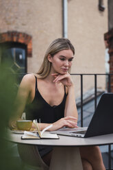 Portrait of young woman sitting on roof terrace using laptop - KKAF02637