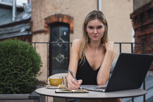 Portrait of young woman sitting on balcony with laptop taking notes - KKAF02640