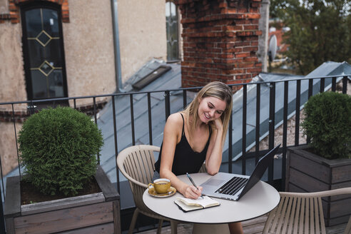 Smiling young woman sitting on balcony with laptop taking notes - KKAF02643