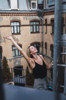 Happy young woman on balcony clambering a fire escape - KKAF02649
