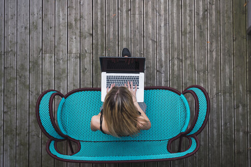 Young woman sitting on turquoise couch on terrace using laptop, top view - KKAF02652