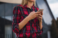Woman wearing plaid shirt holding cell phone, partial view - KKAF02658
