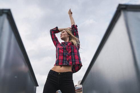 Fashionable young woman on rooftop - KKAF02661