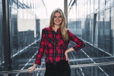 Portrait of smiling young woman wearing plaid shirt - KKAF02667