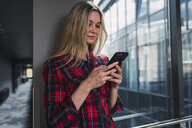 Young woman in modern office building looking at cell phone - KKAF02670