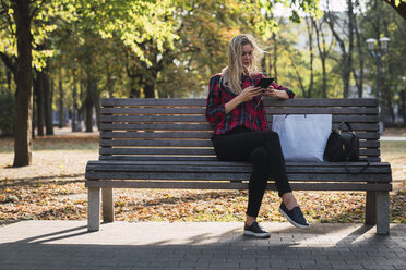 Young woman with shopping bag sitting on bench in autumn using mini tablet - KKAF02685