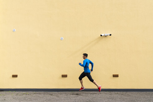 Sportive man running along yellow wall with CCTV camera - KKAF02691
