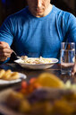 Close-up of athlete eating pasta dish - KKAF02697