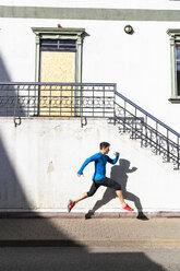 Sportive man exercising on pavement - KKAF02703