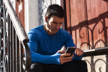 Athlete sitting on front stoop using cell phone - KKAF02709