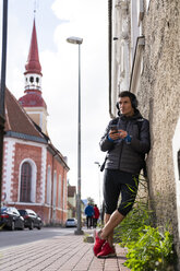 Athlete leaning against house wall with cell phone and headphones - KKAF02712