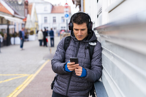 Man leaning against house wall with cell phone and headphones - KKAF02715