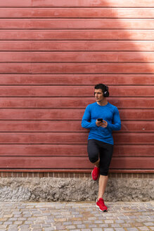 Athlete leaning against house wall holding cell phone - KKAF02718