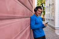 Portrait of smiling athlete leaning against house wall with cell phone and headphones - KKAF02721