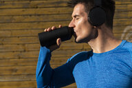 Athlete with headphones drinking from drinking bottle - KKAF02730