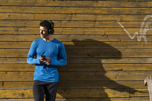 Athlete leaning against house wall with cell phone and headphones - KKAF02733