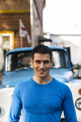 Portrait of smiling man in front of pickup truck - KKAF02736