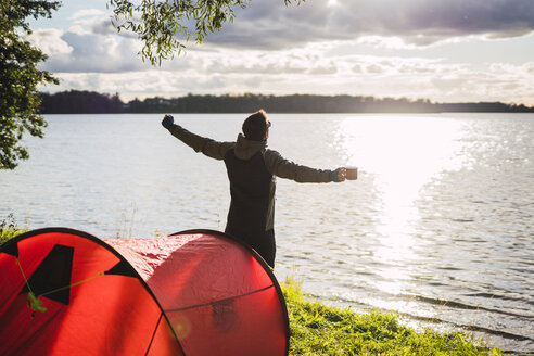 Man camping in Estonia, stretching at lake - KKAF02742