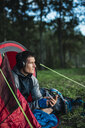 Man camping in Estonia, sitting in his tent, lietsning music from his smartphone - KKA02763