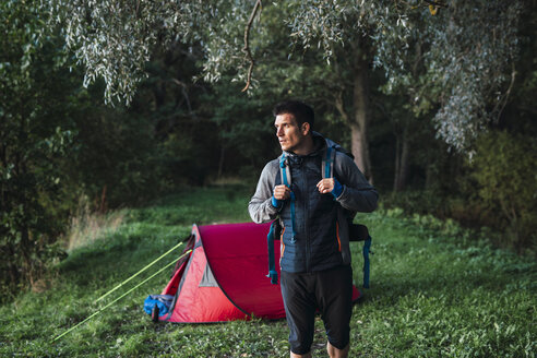 Man camping in Estonia, leaving camp with backpack for a hike - KKA02766