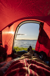 Man camping in Estonia, watching sunset lying in tent - KKA02775