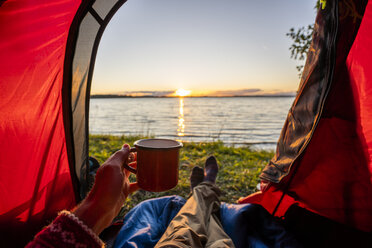 Man camping in Estonia, watching sunset lying in tent - KKA02778