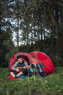 Man camping in Estonia, sitting in his tent, playing the ukulele - KKA02781